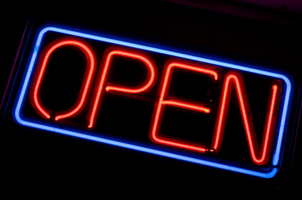 Neon light sign that says open in red lettering in a blue box.