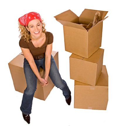Woman sitting on a cardboard box with a bandana in her hair. There is a tall tower of boxes sitting next to her.