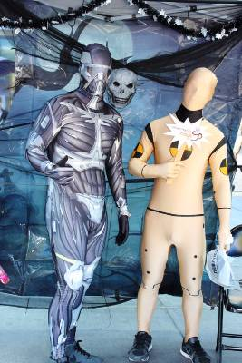 Two figures, one is wearing a grey full body suit with mask and the other is wearing a yellow full body suit with mask